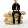 Business man sitting on coins - Stock Photo