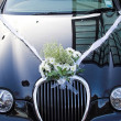 Bouquet on wedding car — Stock Photo
