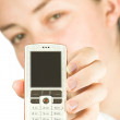 Beautiful woman holding a white cell phone — Stock Photo