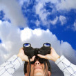 Business man with binoculars over sky - Stock Photo