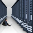 Business man with laptop in a server room - Stock Photo