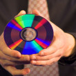 Business hand holding CD — Stock Photo