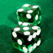 Green dices over felt — Stock Photo