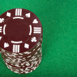 Brown pile of casino chips over green — Stock Photo
