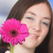 Beautiful girl offering a flower — Stock Photo