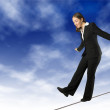 Business woman balancing on rope - Stock Photo