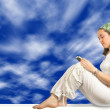 Girl reading a book - sky background - Stock Photo