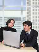 Business couple with laptop in the office — Stock Photo