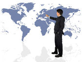 Business man presenting a world map — Stok fotoğraf