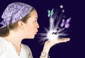 Beautiful girl blowing butterflies - mind reader — Stock Photo