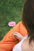 Girl holding a beautiful flower from the back — Stock Photo