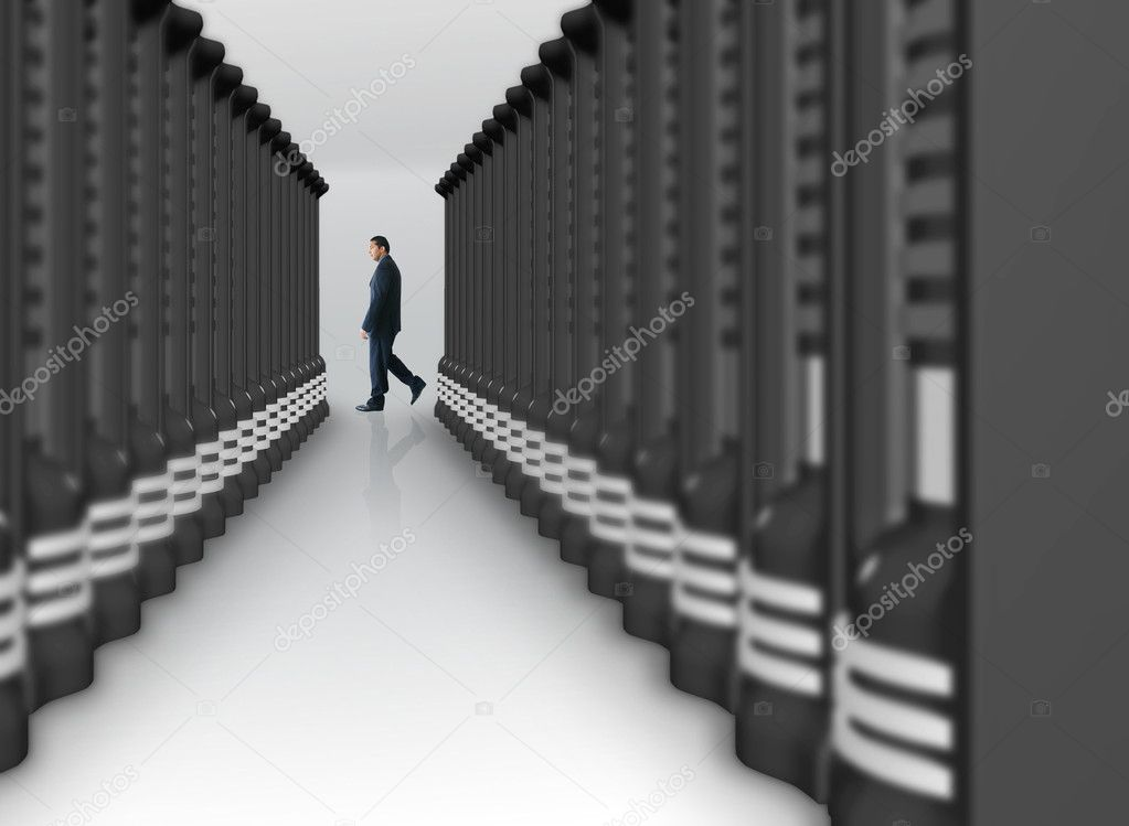 Business man walking by a server room  Stock Photo #7633736