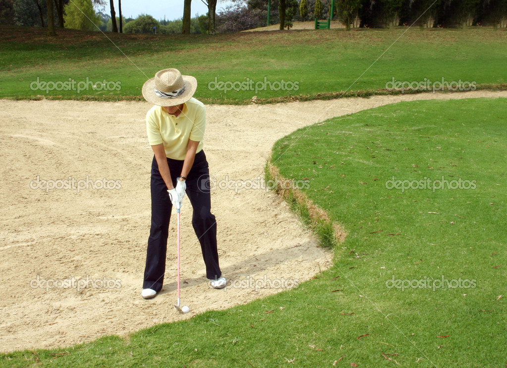 Lady golfer trying to get out of the bunker — Stock Photo #7634495