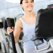 Girl on the xtrainer at the gym — Stock Photo