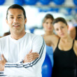 Stock Photo: Gym trainer with group behind