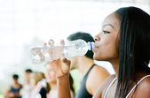 Gym woman drinking water — Stock Photo