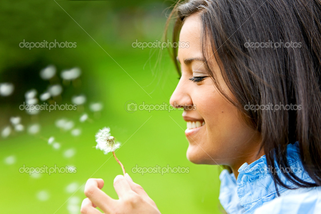 Beautiful woman blowing a flower and smiling — Stock Photo #7643281