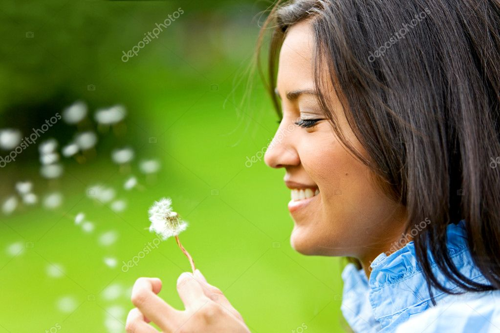 Beautiful woman blowing a flower and smiling — Stok fotoğraf #7643281