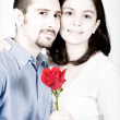Casual couple in love - red flower — Stock Photo