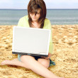 Casual girl using a laptop on the beach — Foto Stock