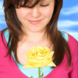 Beautiful teenager with a yellow rose - Stock Photo