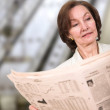 Stock Photo: Business woman reading a newspaper