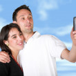 Couple taking a pic with cell phone - Stock Photo