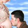 Dad kissing mums belly - Stock Photo