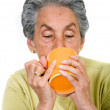 Elderly woman drinking a hot drink - Stock Photo
