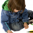 Royalty-Free Stock Photo: Boy colouring on a notebook