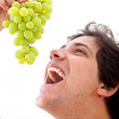 Man eating grapes — Stock Photo