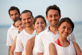 Happy friends at the beach lined up — Stock Photo