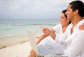 Beach couple on a laptop — Stock Photo