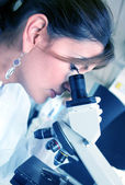 Doctor mirando debajo de un microscopio — Foto de Stock