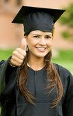 Pulgares arriba mujer de graduación — Foto de Stock