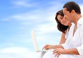 Beach couple on a laptop — Stock Photo