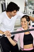 Kobieta na siłowni i trener — Zdjęcie stockowe