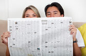 Couple with newspaper — Stock Photo