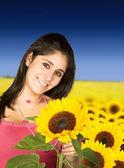 Beautiful girl in sunflower field — Stock Photo