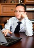 Business man in his office on a laptop — Stock Photo