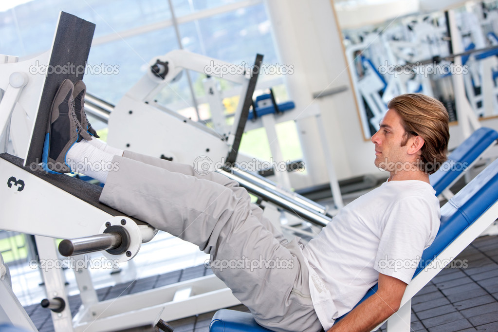 Man exercising his legs with the machines at the gym — Stock Photo #7701891