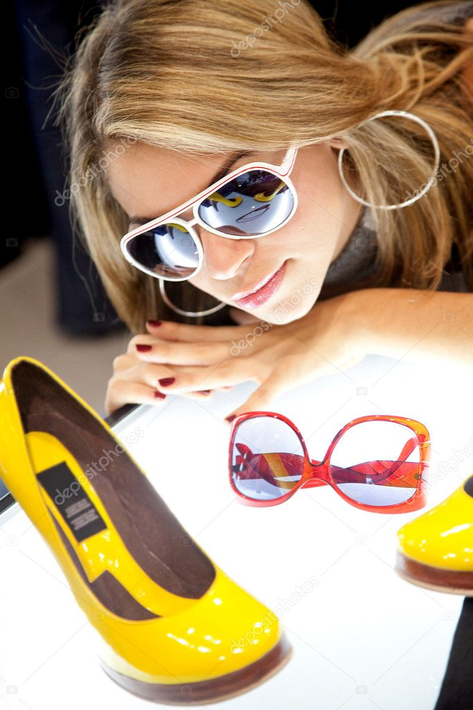 Fashion girl wearing sunglasses staring at some shoes — Stock Photo #7703175