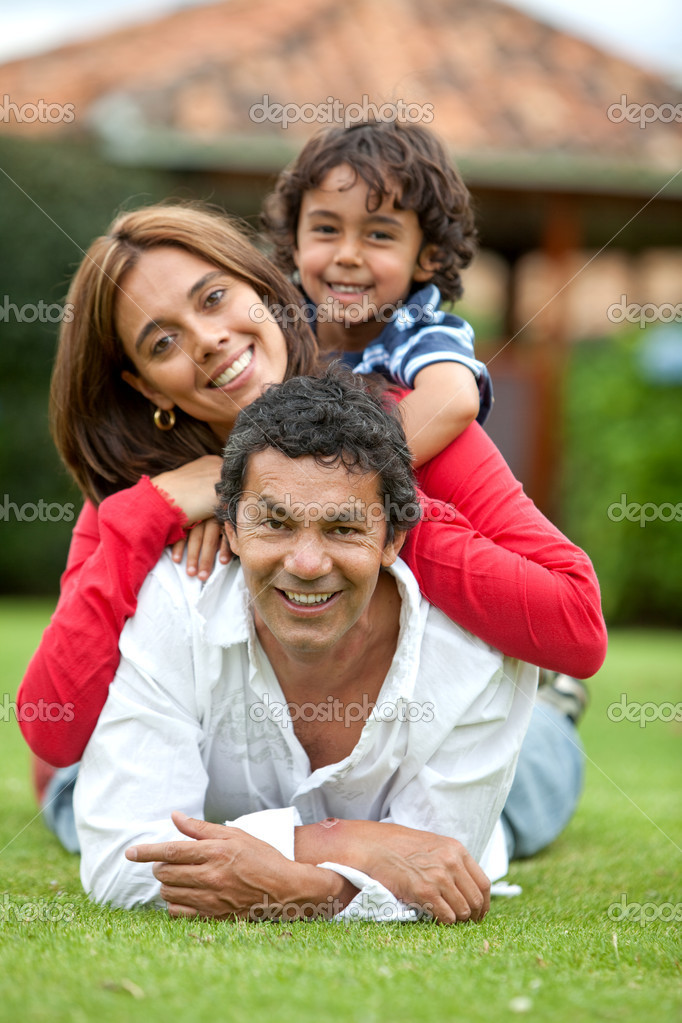 Beautiful family lying on the grass outdoors — Stock Photo #7703964