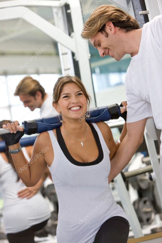 Woman and her trainer doing exercise at the gym  Stock Photo #7704815