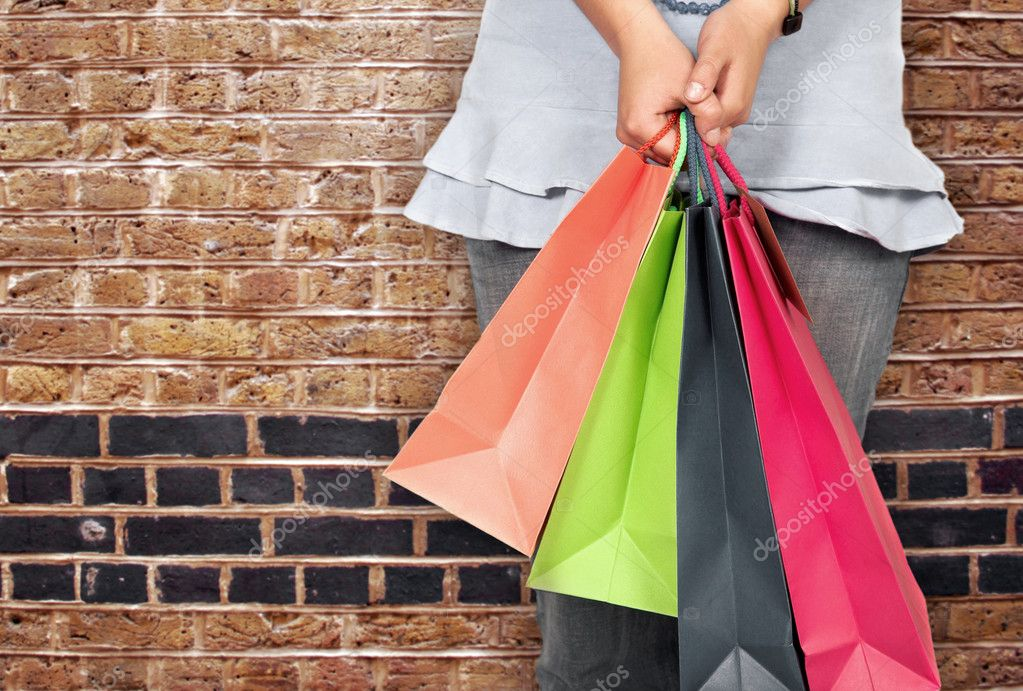 Girl in bright colours holding shopping bags over a brick wall  Stock Photo #7706156