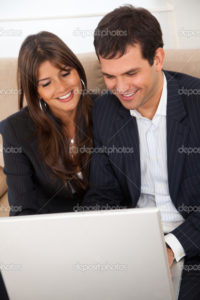 Business couple working on a laptop in an office  Stock Photo #7708488
