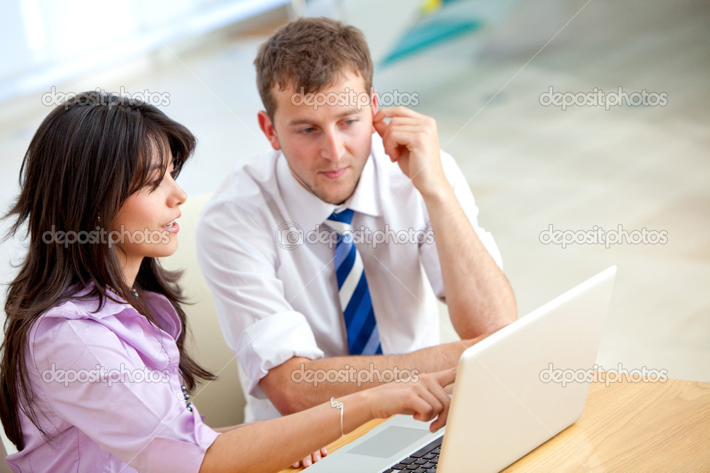 Business couple working on a laptop in an office — Stock Photo #7708715