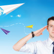 Young man salutes against the blue sky with a paper airplanes — Stock Photo #7710453