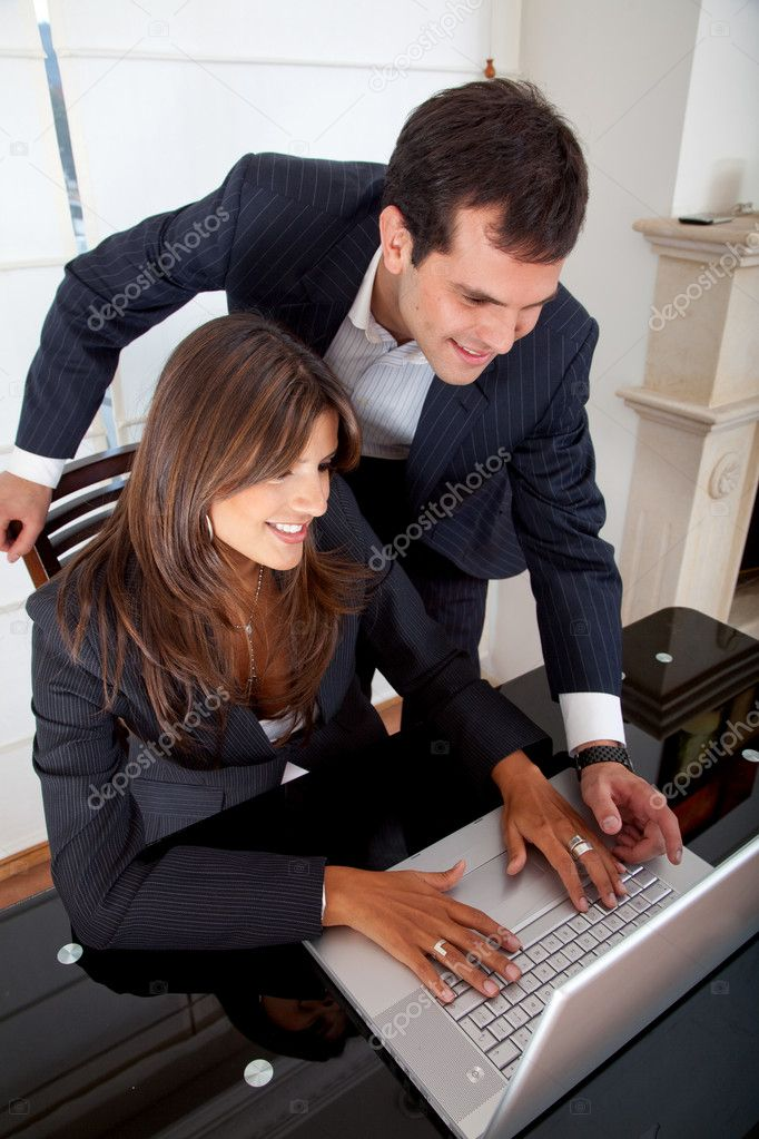 Business couple working on a laptop in an office — Stock Photo #7710048