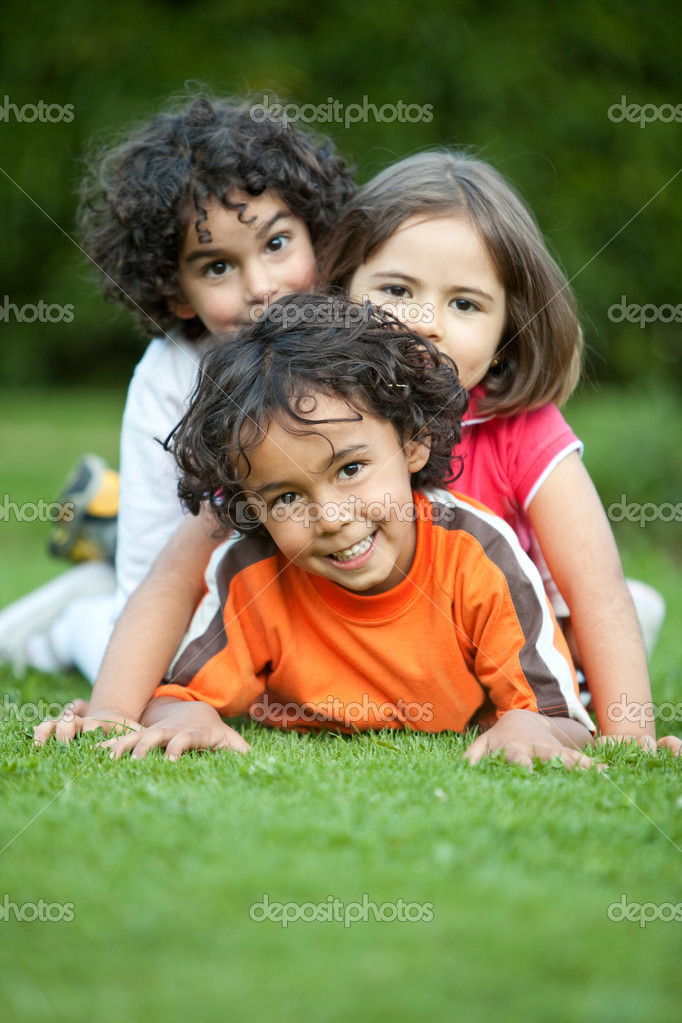 Beautiful playful kids lying on grass outdoors — Foto Stock #7710068